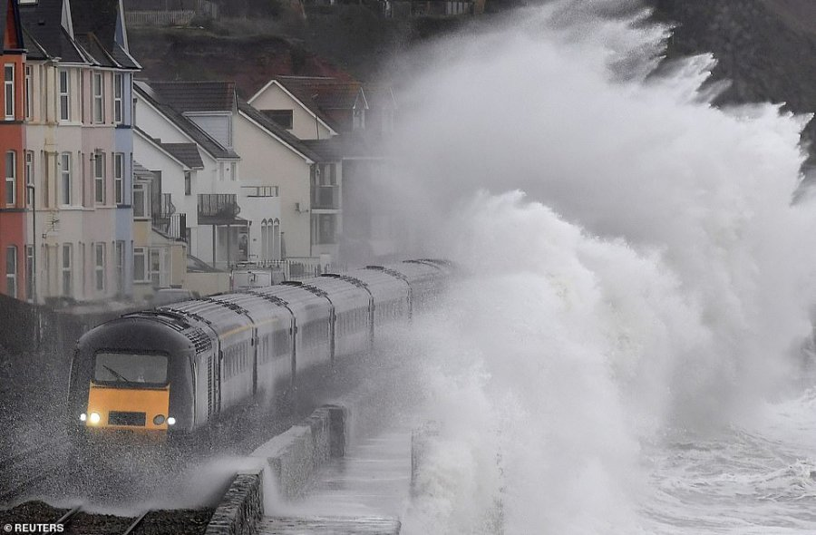Enormous waves crash over a train as it passes through Dawlish on the south coast of Devon on Thursday