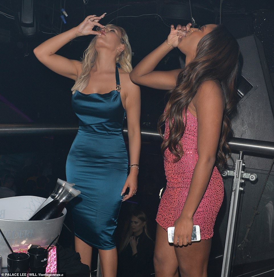 Partners in crime: The two women downed shots as they partied the night away