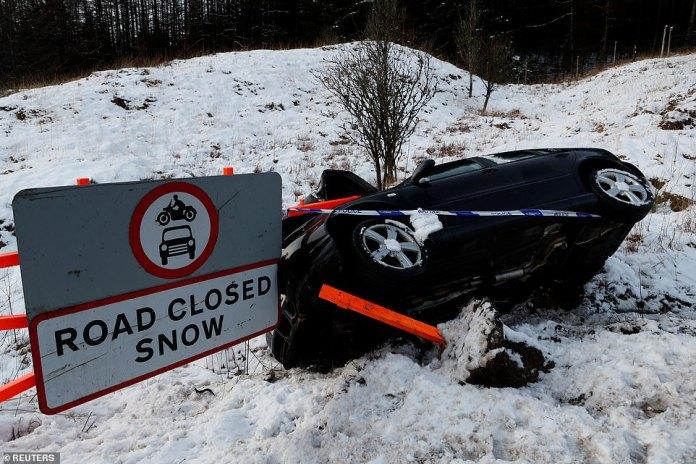 Ein abgestürztes Auto liegt an der Seite der A82 in der Nähe einer Straße, die am Sonntagnachmittag in Tyndrum (Schottland) für Schnee gesperrt ist