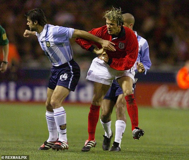 Pochettino and Beckham battling for the ball during their playing careers in an international tie