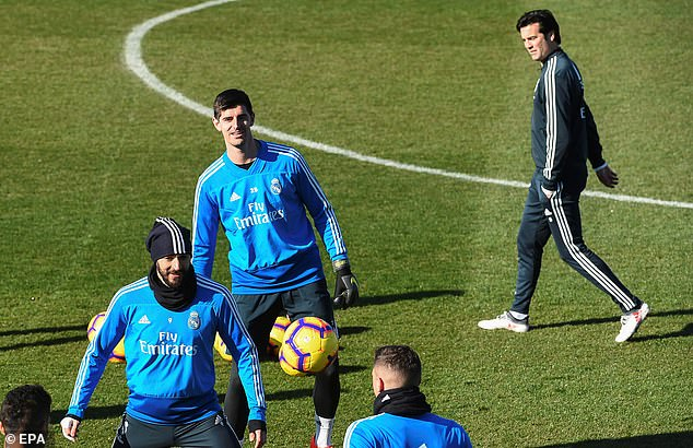 Solari and goalkeeper Thibaut Courtois look on as Karim Benzema looks to control the ball