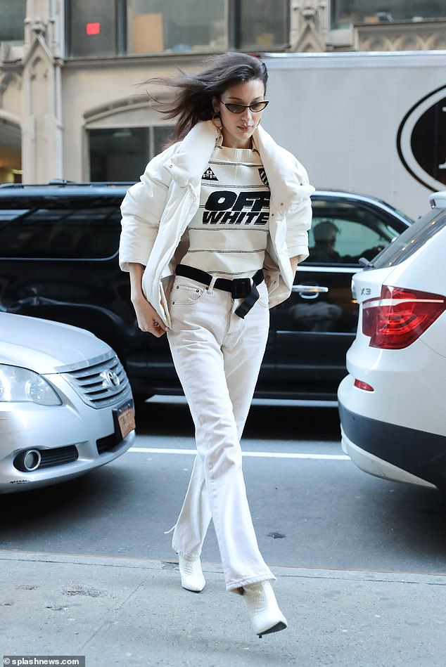 Work: Bella was the picture of style wearing a statement 'Off White' sweater, black belt, and alligator print ankle boots