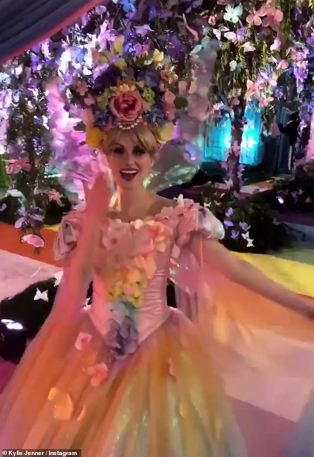 "Enchanting: the princesses with beautiful wreaths of flowers welcomed the people in a ""rainbow butterfly forest"" with colored plants falling from the ceiling"