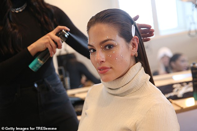 Staying warm: The Nebraska-born model hoisted herself into a cozy-looking long white turtlenecked dress with long sleeves before settling into the makeup chair
