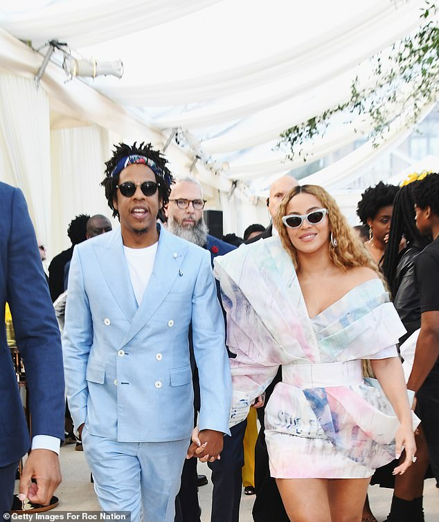 Making it happen:Showing off her knockout legs in a splashy colorful mini, Beyonce, 37, accessorized with earrings and a pair of cat-eye shades