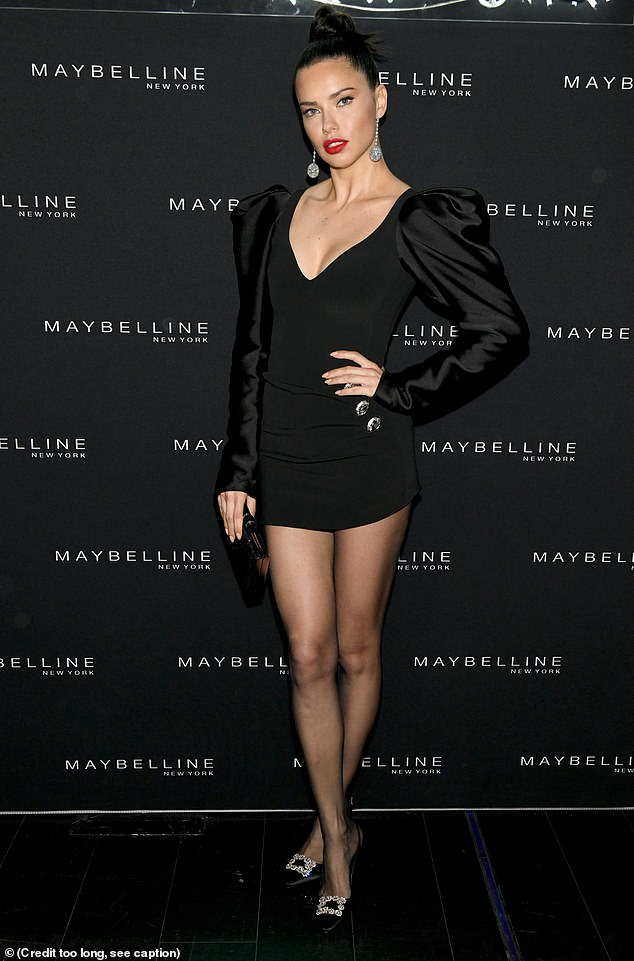 Making it happen:Accessorizing with drop earrings, she shot her best supermodel glare at the camera and balanced on a pair of buckled stilettos in front of the Maybelline backdrop