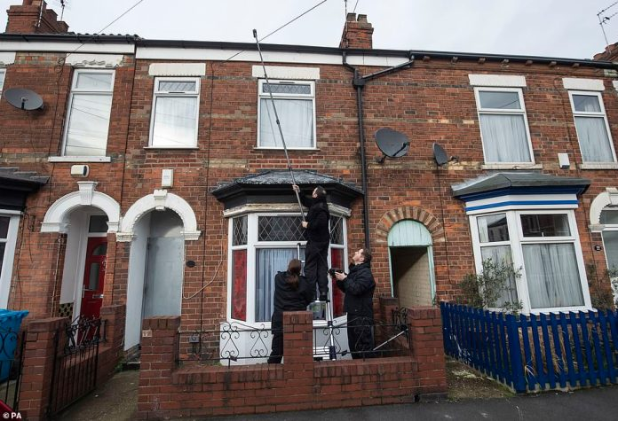 Policemen search Relowicza's property on Raglan Street in Hull with high-tech cameras
