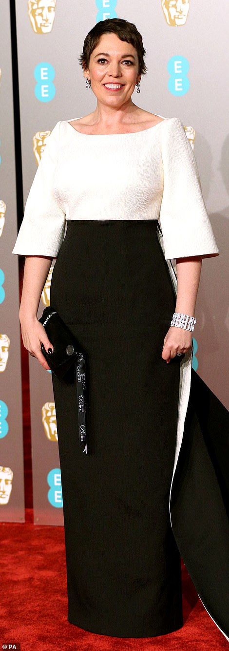 Glam:Olivia accessorised her simple but effective ensemble with a chunky glitzy bangle and a pair of dainty jewel drop earrings, while toting a black leather clutch bang in her hand