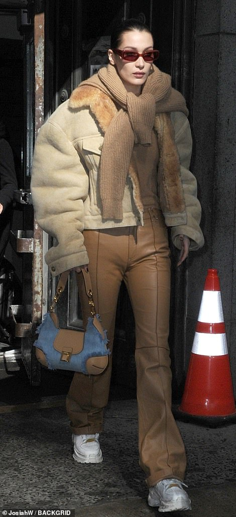 Showing her style:She accessorized with a denim and brown leather designer bag, brown shades, and a camel colored knit sweater tied around her shoulders