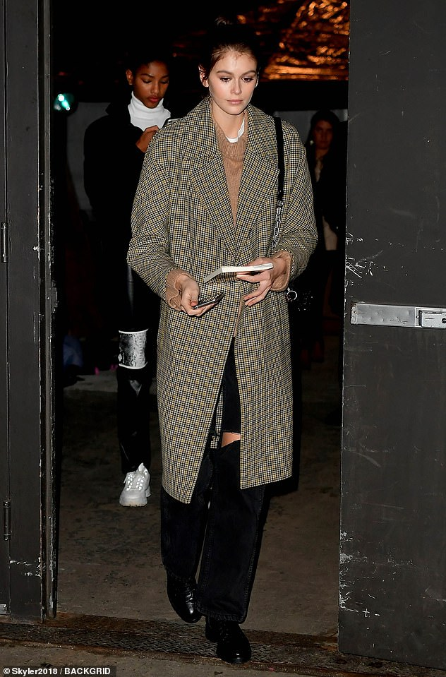 Casual exit: She left the runway show in a checked coat and ripped black denim