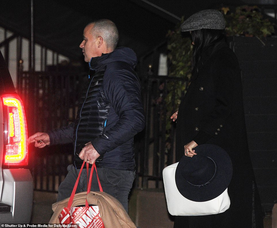 On the go: The bodyguard who walked in front of her also carried some of her things, including another coat, suggesting that Meghan may have brought several outfit options with her