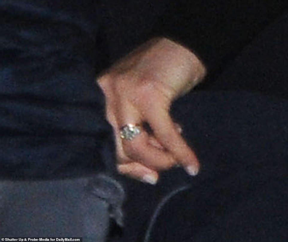 Glitz and glamour: Although Meghan seemed as though she was trying to maintain a low profile, the engagement ring on her finger was unmistakable. The three-stone ring was designed for her especially by her husband Prince Harry