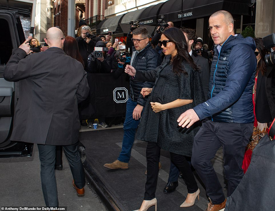 Look out: Meghan flashed a small smile as she made her way to a waiting SUV, which had Department of State plates on it