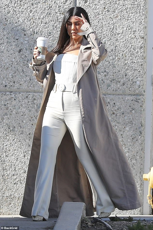 New trench coat: the mother of three wore a pristine white top with a matching white belt, white pants and white heels