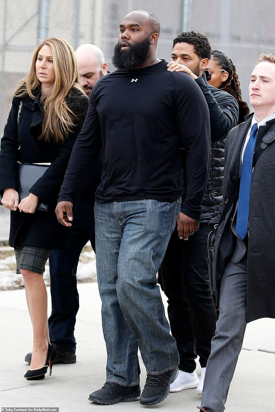 Even before he reached the scrum of photographers, Smollett placed his hands on his security guard's shoulders