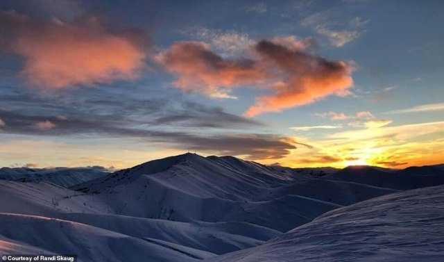 A view of the sun setting over the undulating snowy peaks in the High Atlas Mountains in Morocco
