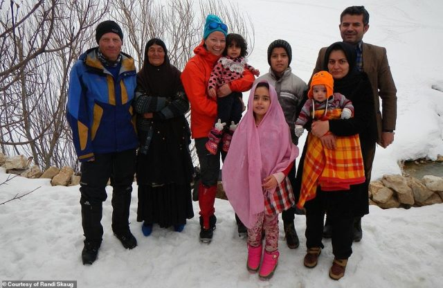 Janne and Brian stand in the snow with a local family. Randi said the people in Iran 'went the extra mile'. She mused: 'They danced with us, served tea with us, they even gave us cake in the middle of the street'
