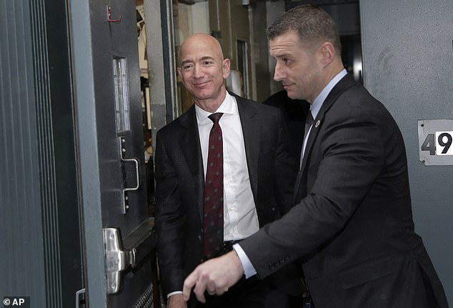 Amazon CEO Jeff Bezos, left, leaves the Yale Club in New York, Wednesday