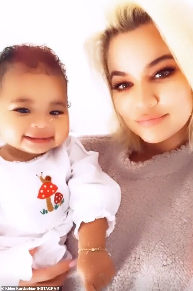 PAIN:Khloe was seen holding True on Sunday. She received the shock of her life when she learned earlier this week that her beau  had been seen 'making out' with Jordyn