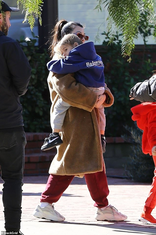 Too much: Kourtney carried her youngest, Reign, four, away from the open-air service