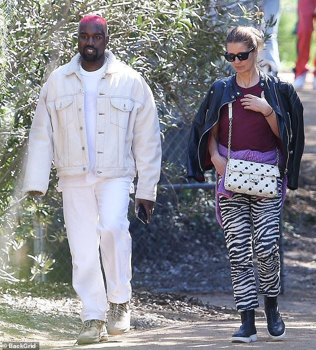 All in white: Kanye had red hair as he was seen with a woman as he walked on a dirt path