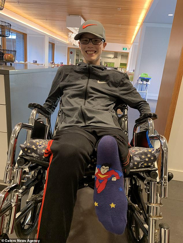 Jacob is now able to use crutches and will be able to use a prosthetic leg once he has gone through rehabilitation. Pictured, showing off his new knee with attention grabbing socks