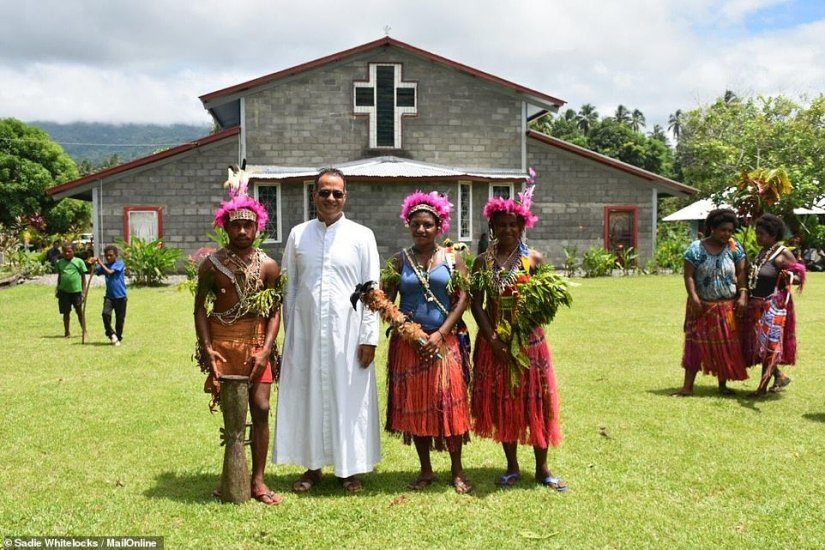 Father Ralph took charge of the Catholic church on the off-grid island of Karkar on May 12 last year. He is originally from the crowded city of Hyderabad in India and he spent years enrolled in religious studies. Above, he poses with members of his congregation as they take part in a traditional ceremony celebrating the inauguration of a new priest in the area