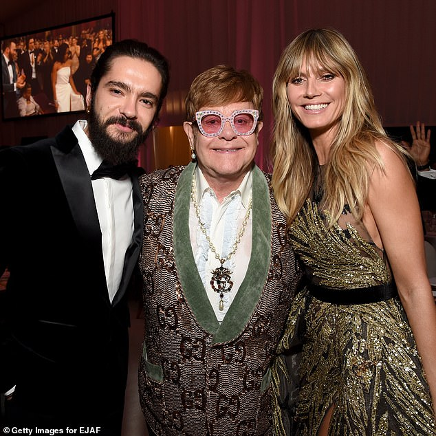 Host with the most: The couple posed alongside Sir Elton John at their first bash of the evening