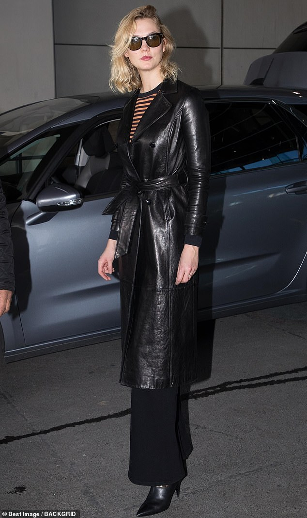 Hell for leather: The supermodel, 26, looked chic in a Matrix-style belted leather mac and tortoiseshell shades