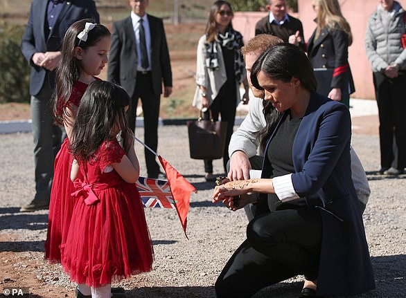 Meghan and Harry's three-day trip has focused on the subject of female empowerment. Above, they walked in without seeing Rania and Rayhana, pictured, who were waving a British and Moroccan flags, but they spotted them as they left and Meghan immediately made a beeline for the sisters and bent down to say hello (pictured)