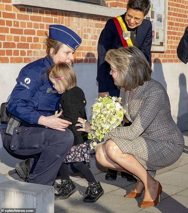The Queen crouched down to speak to a young girl, who appeared shy as she turned away to hug a police officer during a visit to Herentals, Antwerp on Tuesday