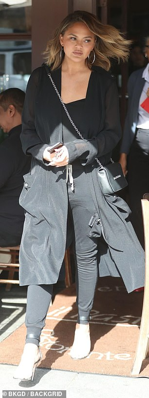 Sleek: Teigen covered up in the brisk weather wearing a long sheer duster with a black tank top and matching cargo pants