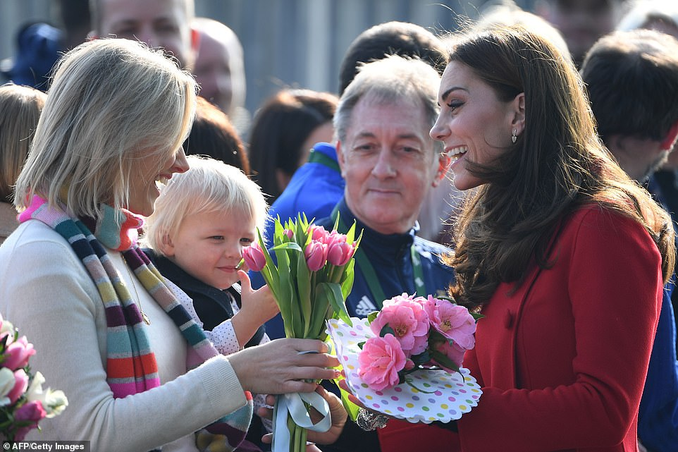 Radiant Kate beamed as she was handed several bouquets of spring blooms by well-wishers in the crowd outside the stadium