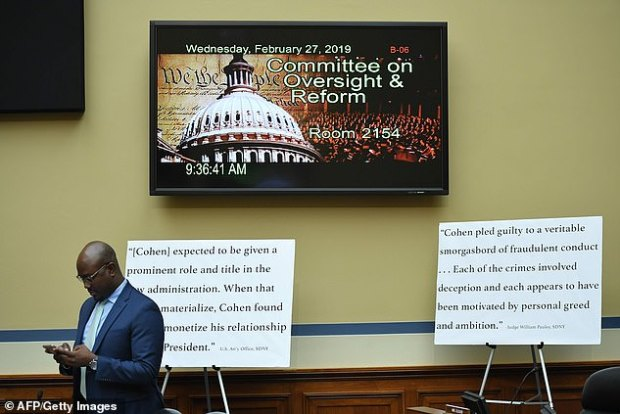 The House Oversight Committee hearin room included display boards brought by Republicans seeking to impeach the former Trump fixer's credibility
