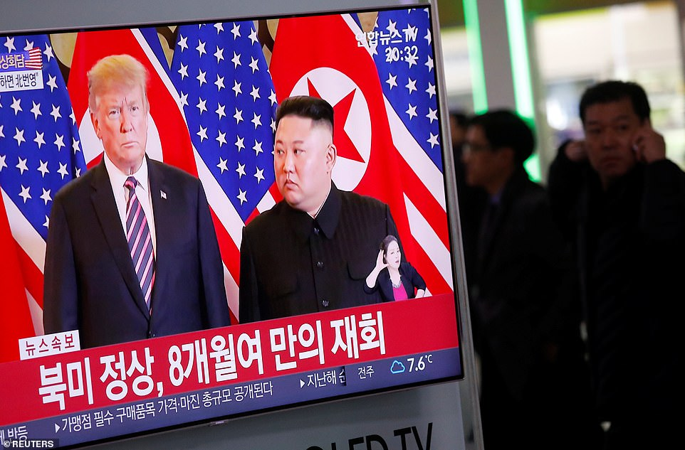 People walk past a TV broadcasting a news report on a meeting between North Korean leader Kim Jong Un and U.S. President Donald Trump, in Seoul, South Korea, February 27, 2019