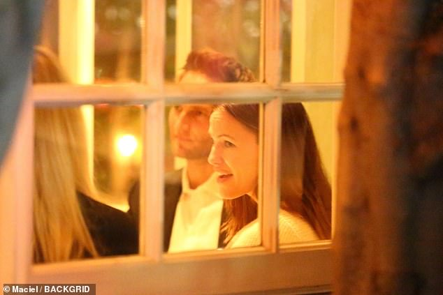 Triple date: The Alias star was seen in a white knitted top as she chatted to a friend next to her with John sitting the other side