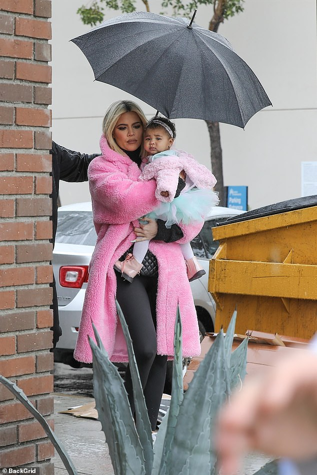 Mama and I: Khloe looked fantastic in an electric pink jacket as she strolled through the rain with True on her hip