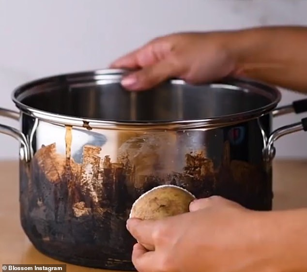 A potato is cut in half before the cut side is dipped into a full bowl of salt and rubbed over the burnt pan