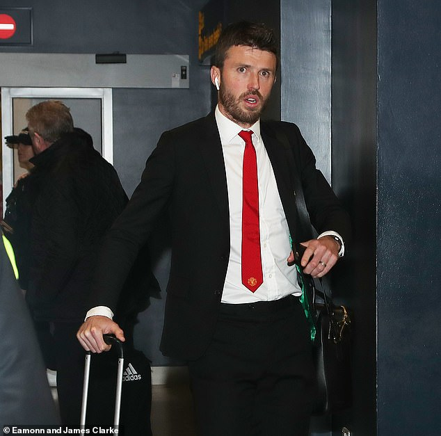 United coach Michael Carrick wore Airpods as he walked through with his luggage in tow