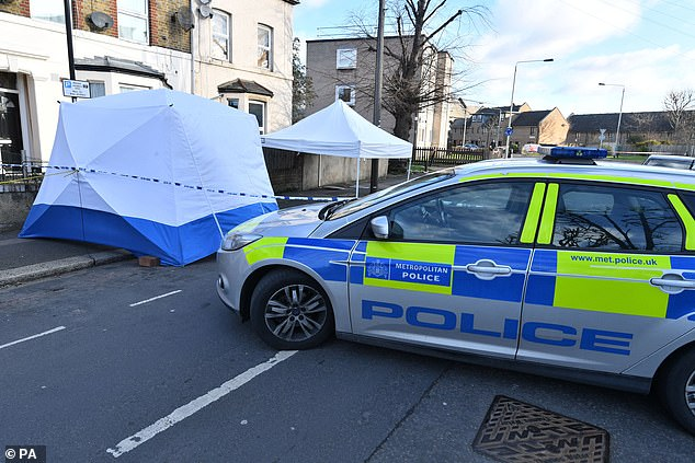 A police tent set up behind the police cordon is covering the crime scene as forensic officers conduct their enquiries