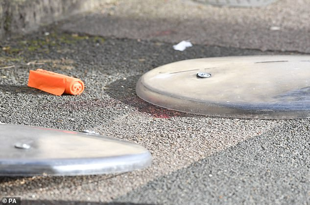 Police riots shields partially cover blood stains onthe pavement at North Birkbeck Road, where the stabbing happened