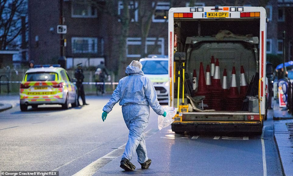 A forensic officer walks towards a van as police examine the crime scene in West Kensington