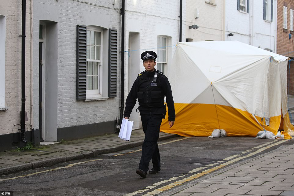 A Met Police officer walks past a forensic tent over the spot where Mr Hassan was stabbed as forensic specialists examine the scene
