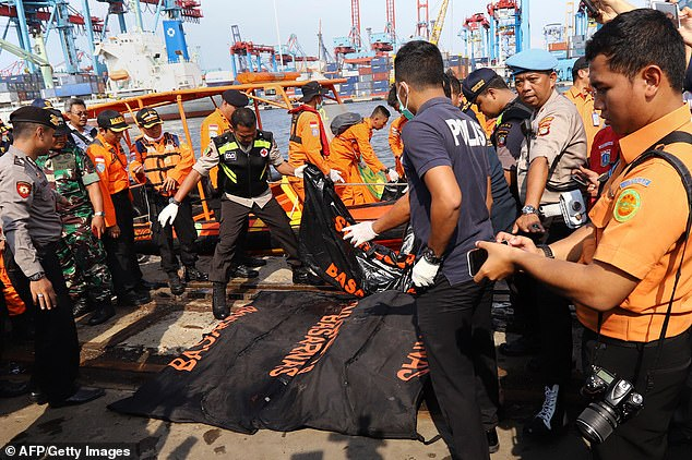 Human remains were placed in body bags after being recovered from the scene of the crash off Indonesia