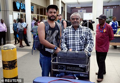 Passenger Ahmed Khalid (left), who missed the doomed Ethiopian Airlines Flight ET 302 while connecting from Dubai, meets his father Khalid Bzambur (right) in Nairobi