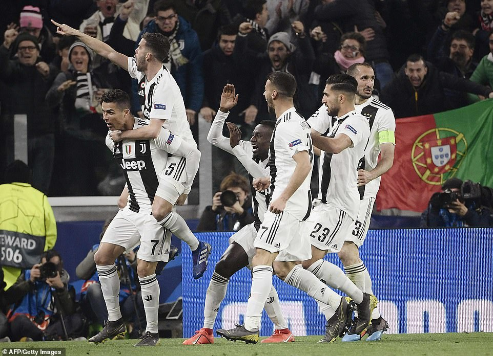 Ronaldo is mobbed by team-mates after his second goal set up a grandstand finish at the Juventus Stadium on Tuesday night