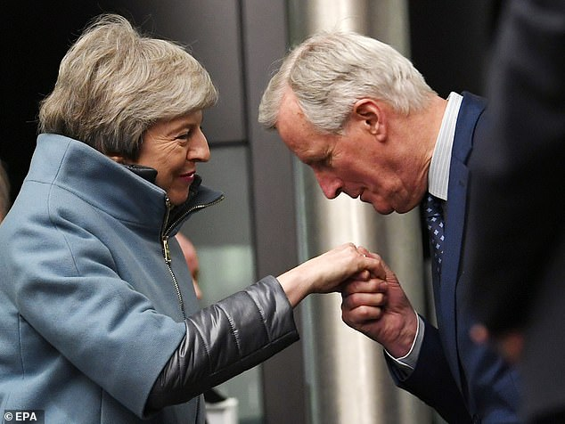 Mr Barnier kisses Mrs May's hand after she arrives at the European Parliament on Monday