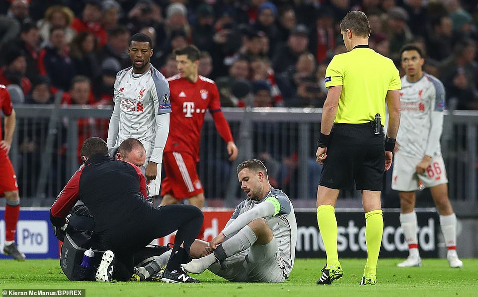 Liverpool skipper Jordan Henderson receives treatment on the pitch after suffering an early injury at the Allianz Arena
