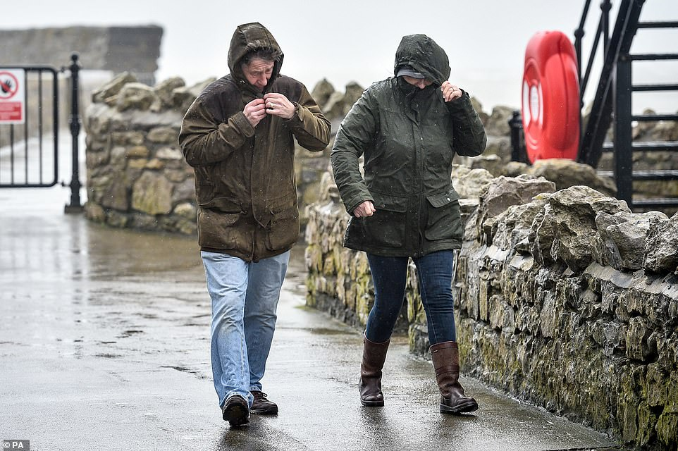 People are plagued by wind and rain yesterday in harsh weather conditions along the Porthcawl harbor wall in South Wales