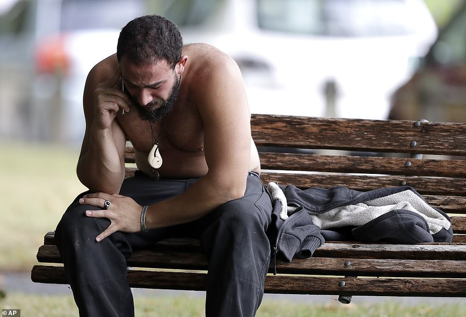 A man reacts as he speaks on a mobile phone near a mosque in central Christchurch, New Zealand